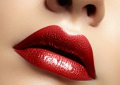 Close-up macro shot of female mouth. Glamour red lips Makeup with sensuality gesture. Metalic gloss lipstick. Full lips poster