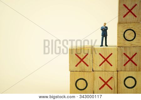 Businessman Miniature Standing And Thinking On O X Board Games. (tic Tac Toe). Business Direction An