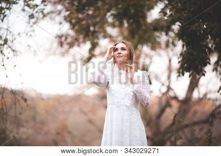 Stylish Girl 20-24 Year Old Wearing Elegant White Dress Holding Magic Lamp With Glowing Lights Posin