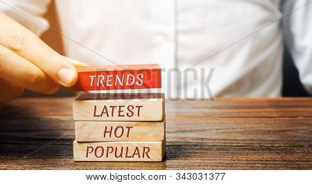 Businessman Puts Wooden Blocks With The Words Trends, Latest, Hot, Popular. Popular And Relevant Top