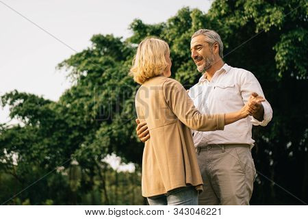 Senior elegant caucasian couple dancing looking at each other feeling love and cherish on their anniversary in the park with copy space, happily retired spouse, well-managed retirement life concept. poster