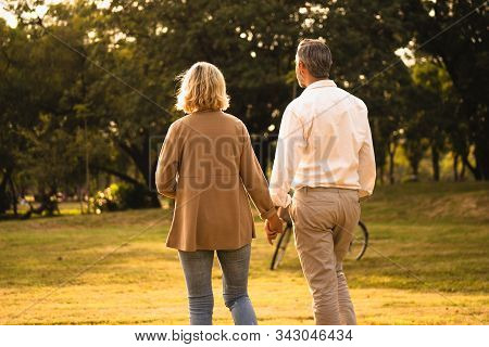 Silhouette Back View Of Caucasian Mature Couple Holding Hand Spend Time Together Walking Relaxing At