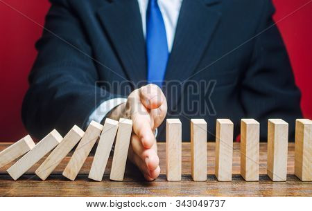 Businessman Stops Domino Falling. Risk Management Concept. Successful Strong Business And Problem So