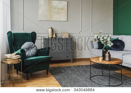 White Flowers In Vase On Coffee Table In Luxury Living Room Interior With Grey Couch