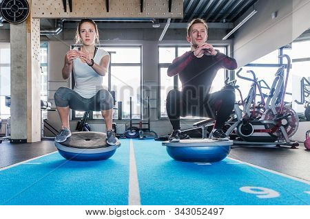 Fit Couple Working On Bosu Ball In Fitness Studio. Doing A Squat Exercise