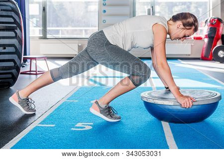 Concentration Sporty Young Athletic Woman In Gray Leggings And White T-shirt Working In Gym Doing Pl