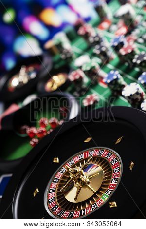 Casino Theme, Close Up Of Roulette, Red And Black Numbers, Stack Of Chips As Background.