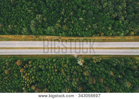 Aerial View Of Highway Road Through Green Forest Landscape In Summer. Top View Flat View Of Highway