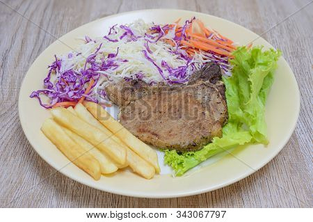 Grilled Steak With Fries On The Floor, A Plate Placed On A Wooden Table