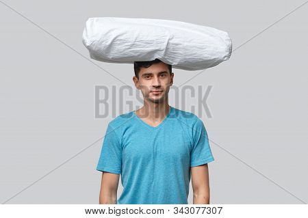 White Pillow Lies On A Head Of Tired Brunet Man In A Blue Tee Isolated Over Grey Background. Need To