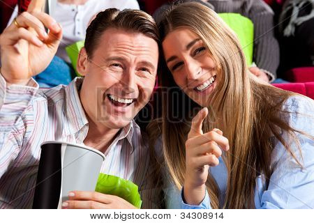 Couple in cinema watching a movie, it seems to be a funny movie
