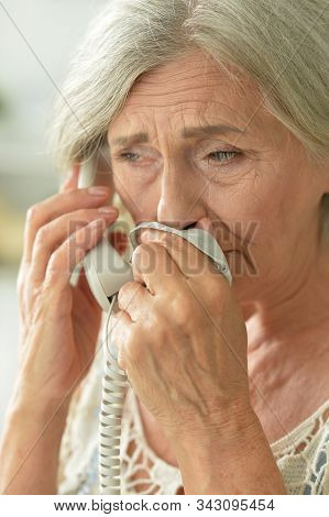 Close Up Portrait Of Upset Senior Woman Calling Doctor
