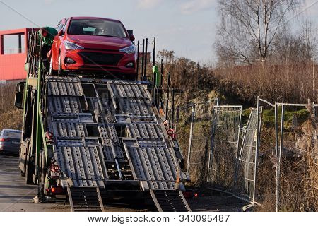 Krakow, Poland 20.12.2019: The Process Of Unloading The Car Truck. A Small City Red Car Is Being Pre