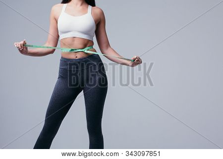 Slender Young Woman Measures Her Slim Waist With A Tape Measure, Closeup In A White Tank Top And Gra