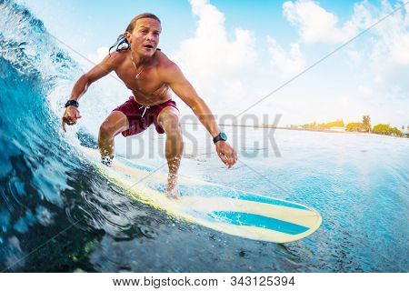 Young surfer rides the ocean wave in Maldives