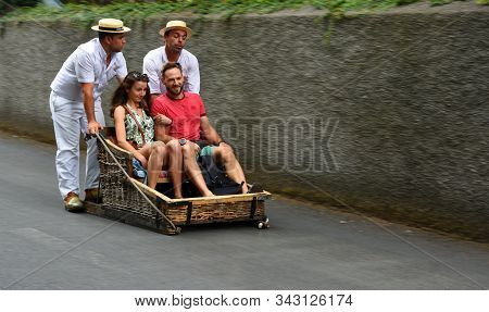 Funchal, Madeira, Portugal  -  June 26, 2019:  Funchal  Madeira  Couple Having Downhill  Basket Ride