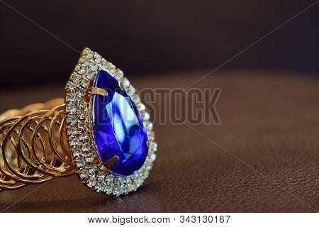 Gold Bangle Blue Gemstone Surrounded By Luxurious Diamonds