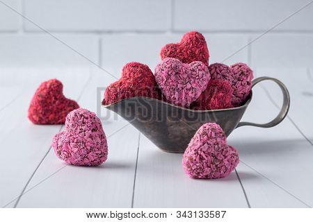 Heart Shaped Energy Bites For Valentine's Day In Gravy Boat On White Wooden Table