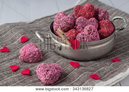 Heart Shaped Energy Bites For Valentine's Day In Small Saucepan On Grey Cloth