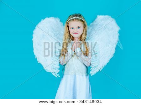 Face Of Beautiful Little Angel Girl On Color Background. Looks Like An Angel. Angels Little Hands Cr