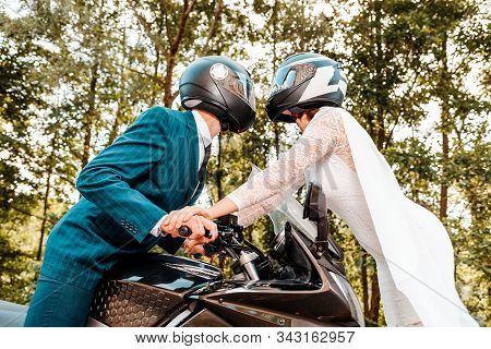 Wedding, newlyweds. A man and a woman in wedding dresses and motorcycle helmets are attracted to each other. A man is sitting on a motorcycle, and a woman is standing in front of him. Close up poster