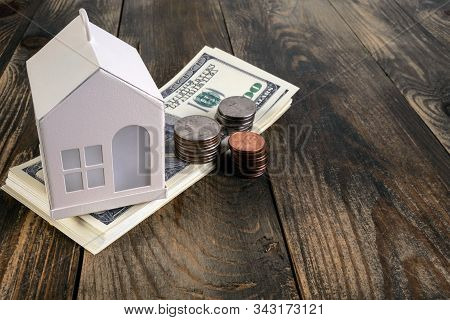 Mortgage Or Home Ownership Investment Concept. Money And White Toy House On Table. Us Dollars And Co