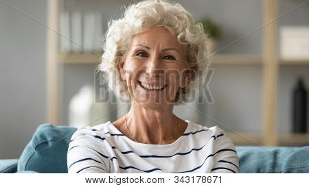 Headshot Portrait Elderly Woman Resting On Couch Looking At Camera
