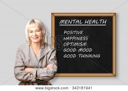 Smiling Woman Psychologist Standing Near Board With Text, Mental Health.  Mental Health Begins With