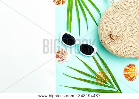 Travel Accessories. Wicker Handbag And White  Sunglasses On A Blue And White Background. Copy Space