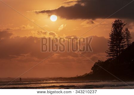 Sunrise In The Skies At Burleigh Heads With The Silhouette Pine Trees And Headland, Gold Coast.