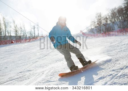 Man Snowboarder Snowboarding On Fresh White Snow On Ski Slope On Sunny Winter Day Snowboarder Balanc