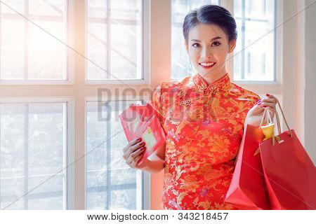 Happy Chinese Woman Wearing A Qipao Dress Traditional Or Cheongsam Is Showing A Lot Of Red Envelopes