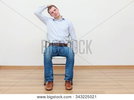 Caucasian man, sitting on chair, stretching neck - front