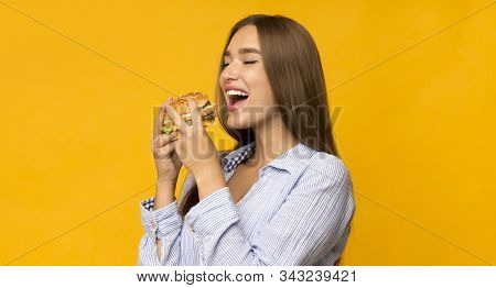 Cheat Meal Day. Hungry Young Woman Eating Burger Standing In Studio On Yellow Background. Panorama