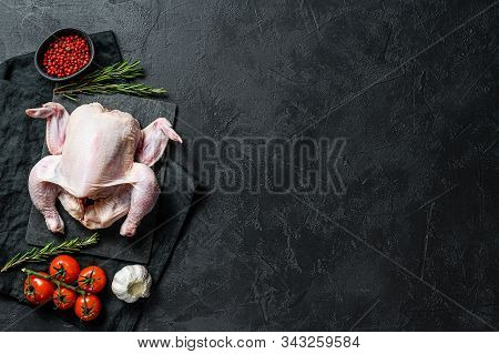 Raw Whole Chicken With Rosemary And Pink Pepper. Black Background. Top View. Space For Text