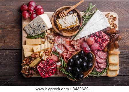 Meat And Cheese Plate.traditional Italian Antipasto. Assorted Cheeses On Wooden Cutting Board. Brie