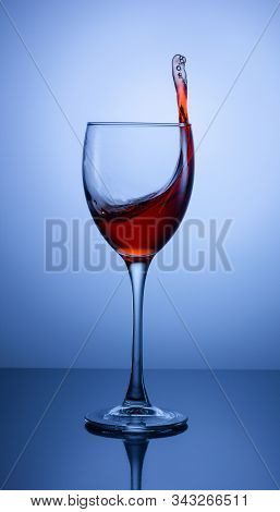 Beautiful Splash In A Glass Of Red Wine On A Gradient Background