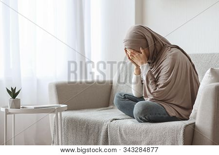 Depression Concept. Upset Muslim Woman In Hijab Crying On Sofa At Home, Hiding Her Face In Hands, Fe