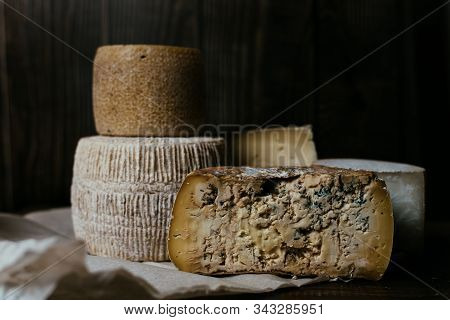 Different Homemade Cheeses On A Dark Wooden Background. Pieces And Cheese Heads Of Gorgonzola, Asiag