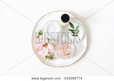 Styled Beauty Composition. Skin Cream, Shampoo Bottle, Rose Flowers And Himalayan Salt. White Table
