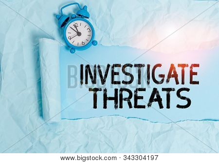 Handwriting text writing Investigate Threats. Concept meaning carry out a systematic inquiry on potential danger Alarm clock and torn cardboard placed above plain pastel table backdrop. poster