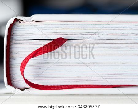 Closed Book With A Bookmark In The Form Of A Red Ribbon Close-up. The Book Is A Source Of Knowledge