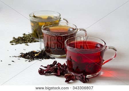 Three Glass Cups With Black, Red And Green Tea With Dry Leaves On A White Background. Red Hot Hibisc