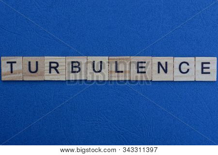 Gray Word Turbulence From Small Wooden Letters On A Blue Table