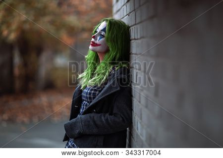 Portrait Of A Greenhaired Girl In Chekered Dress With Joker Makeup On A Brick Wall Background.