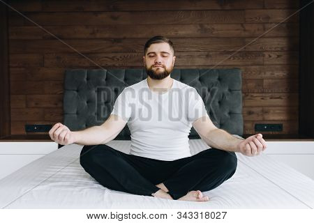 Handsome Caucasian Man Meditating Calmly And Being Mindful On His Bed In Bedroom
