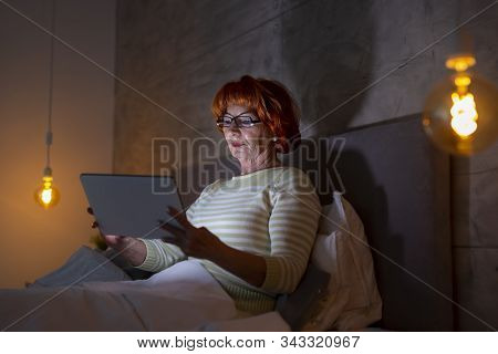 Beautiful Senior Woman Wearing Pajamas Sitting In Bed, Reading An Ebook On Tablet Computer