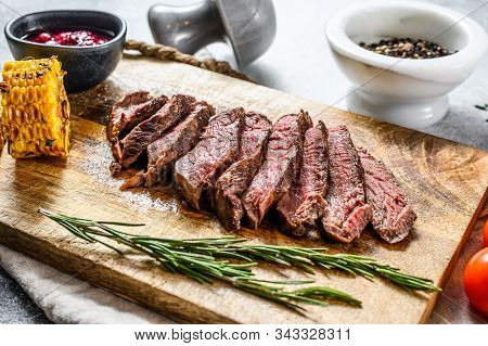 Sliced Grilled Filet Mignon Steak On A Wooden Chopping Board. Beef Tenderloin. Gray Background. Top