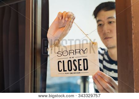 Through Glass View Of Asian Male Business Owner Hanging Up Sign With Inscription Closed At End Of Wo