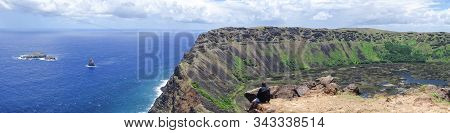 A Man Sits On The Edge Of The Rano Kau Crater On Easter Island, Chile Overlooking The Pacific Ocean;